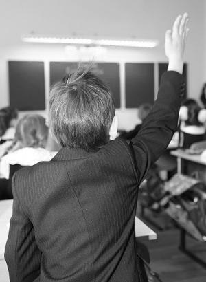 Elementary school student raising hands.